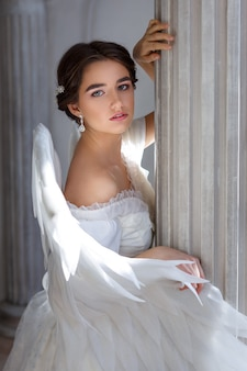 Retrato de una bella joven con un vestido blanco y alas de ángel, de pie con una mirada suplicante contra el fondo de una pared con columnas y flores.