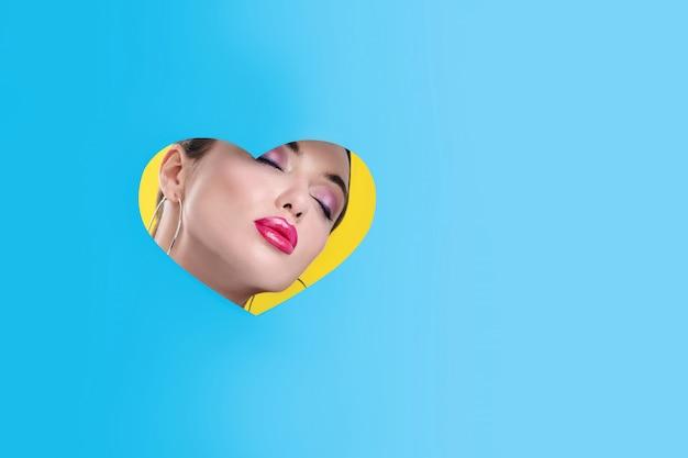 Retrato de una bella modelo con maquillaje de ojos brillantes y labios de color rosa brillante y aretes largos posando en un corazón tallado