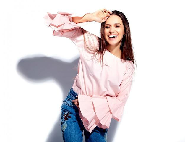 Retrato de la bella modelo de mujer morena caucásica sonriente en blusa rosa brillante y elegantes jeans de verano con estampado de flores
