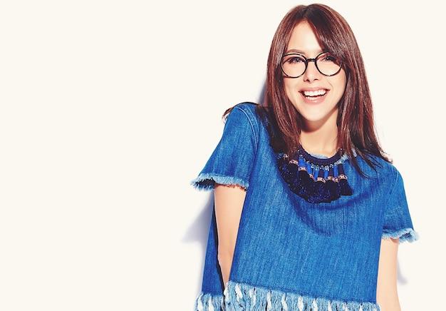 Retrato de la bella modelo de mujer morena inconformista sonriente inteligente en ropa casual con estilo azul jeans y gafas aislados en blanco