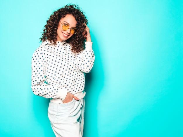 Retrato de la bella modelo sonriente con peinado afro rizos vestido con ropa hipster de verano. mujer divertida y positiva de moda con capucha blanca