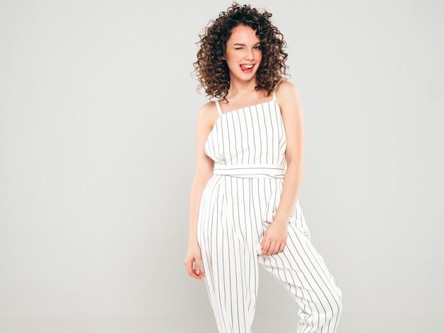 Retrato de bella modelo sonriente con peinado afro rizos vestido con ropa hipster de verano. mujer divertida y positiva de moda muestra lengua