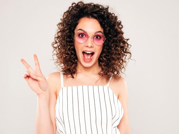 Retrato de la bella modelo sonriente con peinado afro rizos vestido con ropa hipster de verano. la mujer divertida y positiva de moda muestra el signo de la paz