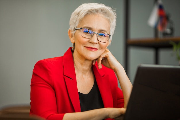 Retrato de una bella mujer adulta en traje con laptop