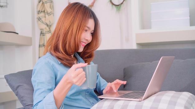 Retrato de una bella mujer asiática atractiva que usa una computadora o una computadora portátil sosteniendo una taza de café caliente