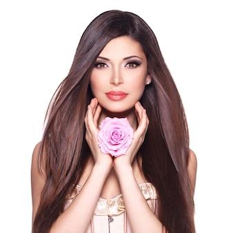 Retrato de una bella mujer blanca con pelo largo y liso y rosa en la cara.