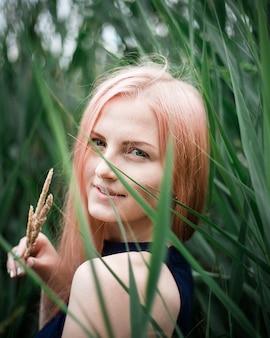 Retrato de una bella mujer de cabello rosado al aire libre en el parque