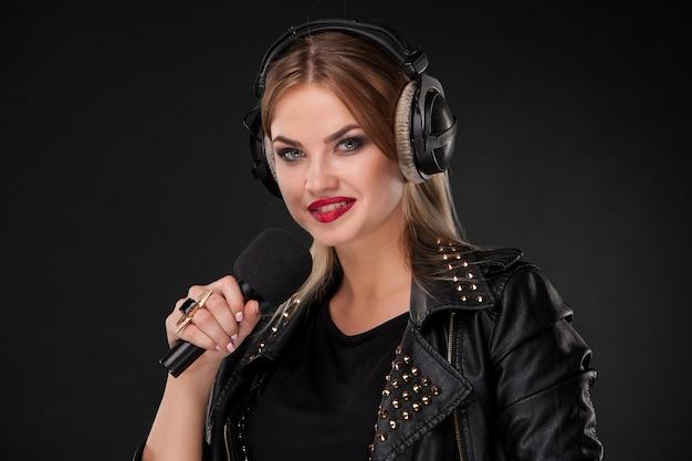 Retrato de una bella mujer cantando en el micrófono con auriculares en estudio sobre fondo negro