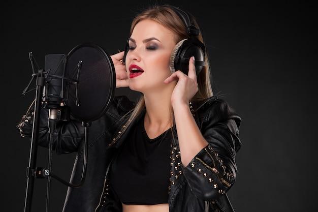 Retrato de una bella mujer cantando en el micrófono con auriculares