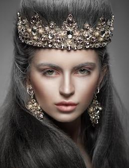 Retrato de una bella mujer en la corona de diamantes y aretes