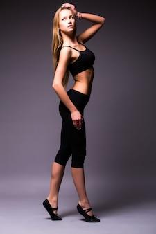 Retrato de una bella mujer deportiva con las manos en las caderas en la pared gris