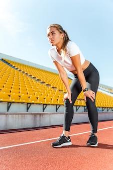 Retrato de una bella mujer descansando después de correr en el estadio