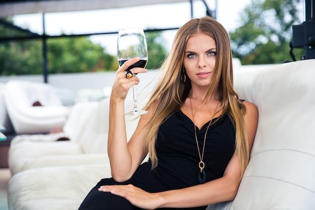 Retrato de una bella mujer elegante sentada en el restaurante con una copa de vino