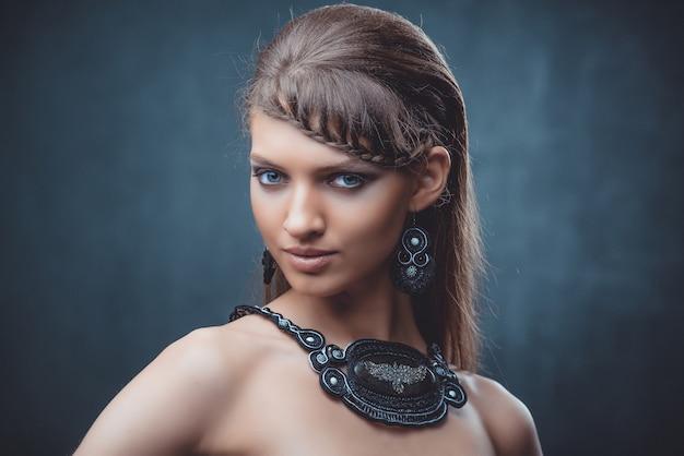 Retrato de una bella mujer con hermoso maquillaje y peinado. con la decoración de una gran piedra.