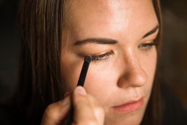 Retrato de una bella mujer joven aplicar sombra de ojos