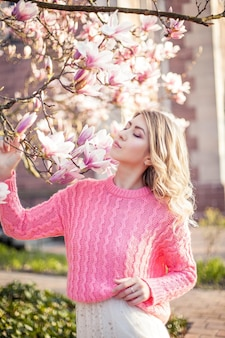 Retrato de una bella mujer joven cerca de una magnolia. primavera.