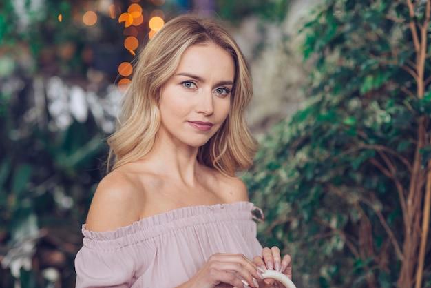 Retrato de una bella mujer joven contra plantas borrosas