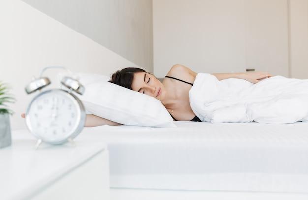 Retrato de una bella mujer joven durmiendo en la cama