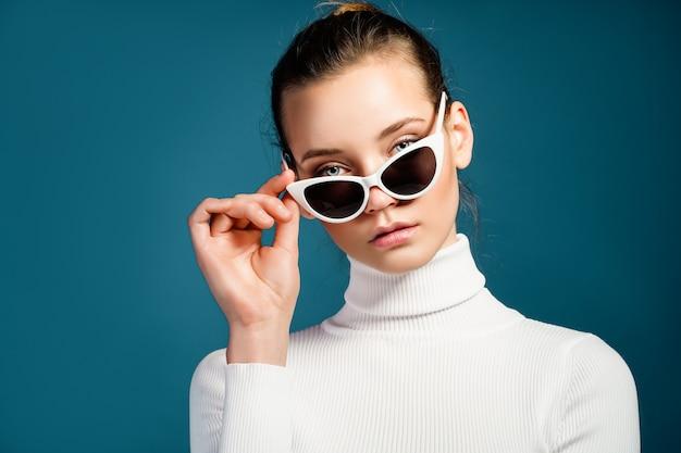 Retrato de una bella mujer joven con gafas de sol