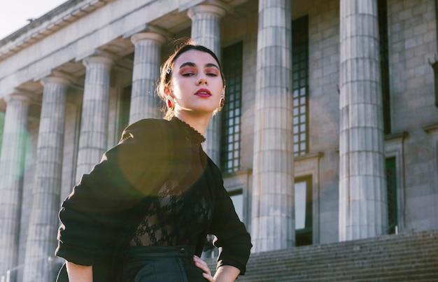 Retrato de una bella mujer joven con las manos en la cadera frente a la columnata