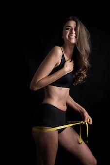 Retrato de una bella mujer joven midiendo su tamaño de figura con cinta métrica