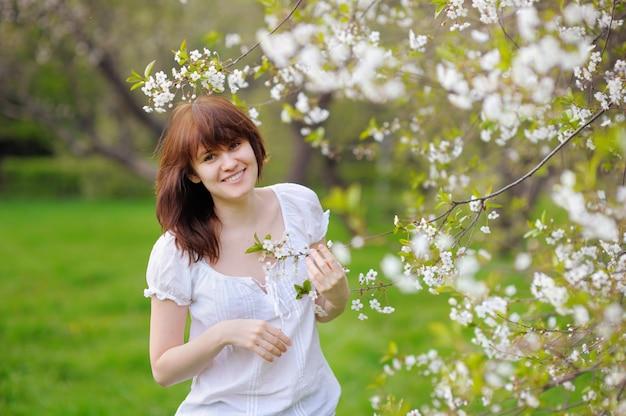 Retrato de una bella mujer joven en el parque de la primavera