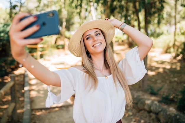 Retrato de una bella mujer joven selfie en el parque con un teléfono inteligente