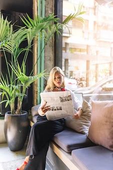 Retrato de una bella mujer joven sentada en una cafetería leyendo un periódico