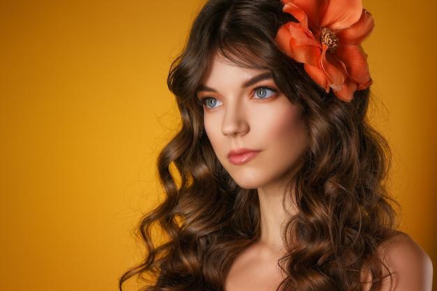 Retrato de una bella mujer joven sobre un fondo amarillo,