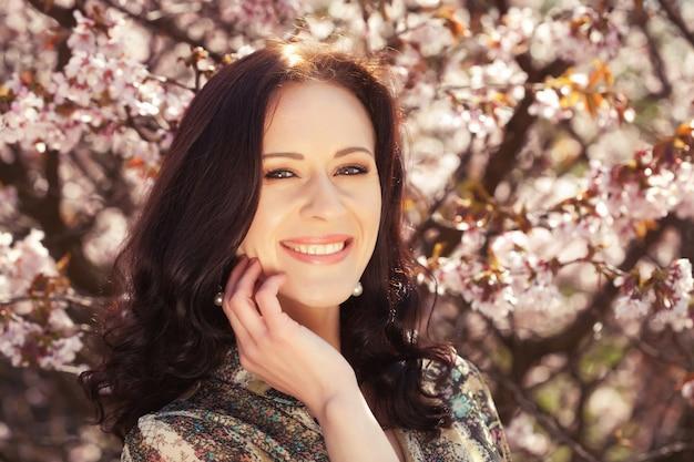 Retrato de una bella mujer joven sobre un fondo de flores de cerezo rosa en primavera