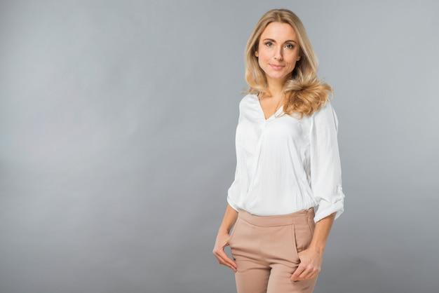 Retrato de una bella mujer joven con sus manos en el bolsillo contra el fondo gris