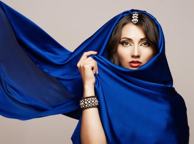 Retrato de una bella mujer joven en tela azul