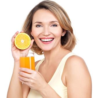 Retrato de una bella mujer joven con un vaso de jugo y naranja aislado en blanco.