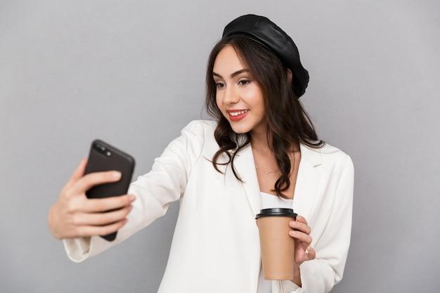 Retrato de una bella mujer joven vestida con chaqueta sobre fondo gris, sosteniendo una taza de café, tomando un selfie con teléfono móvil