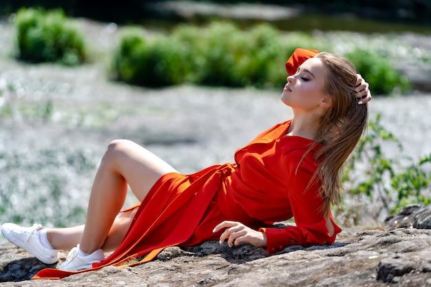 Retrato de una bella mujer joven en vestido largo rojo. vista al lago. fondo de naturaleza. pelo largo. buen maquillaje. sesión de fotos profesional de verano. de cerca. chica sentada sobre una roca, piernas largas y hermosas.