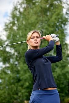 Retrato de una bella mujer jugando al golf en un campo verde al aire libre. el concepto de golf, la búsqueda de la excelencia, la excelencia personal, el deporte real.