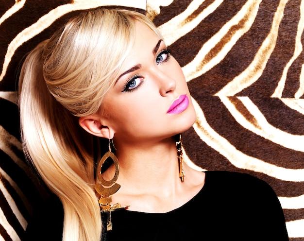 Retrato de una bella mujer con maquillaje de moda en la cara y largos pelos blancos.
