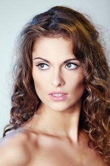 Retrato de una bella mujer morena con cabello rizado y hombros desnudos posando sobre un fondo claro