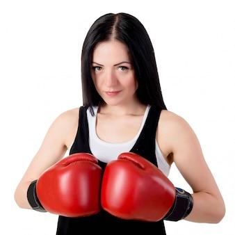Retrato de una bella mujer morena con guantes de boxeo rojos.
