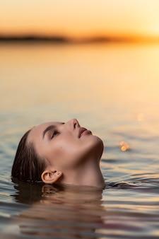 Retrato de una bella mujer con el pelo mojado con el telón de fondo del mar y la puesta de sol. mujer joven con estilo de moda