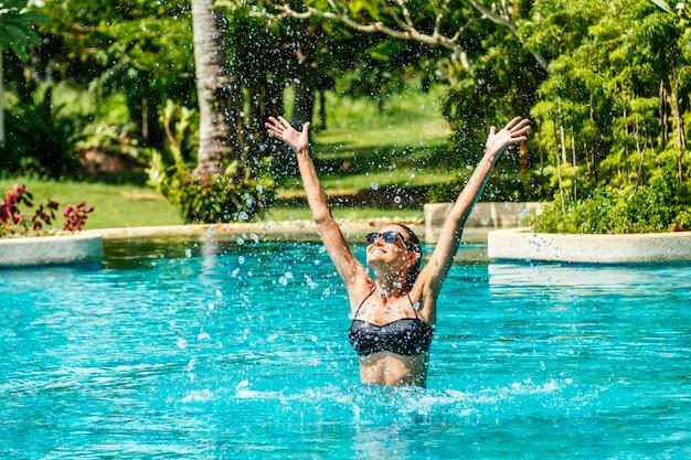 Retrato de una bella mujer en la piscina