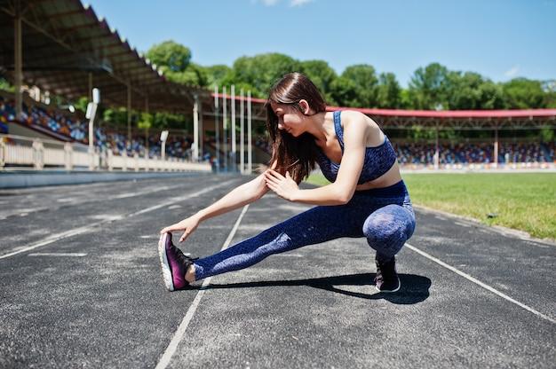Retrato de una bella mujer en ropa deportiva estirando sus músculos en el estadio.