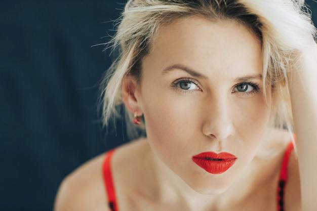 Retrato de una bella mujer rubia con un lápiz labial rojo en sus labios