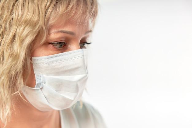 Retrato de una bella mujer rubia con una máscara médica