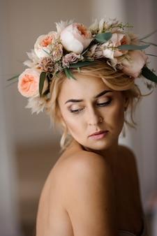 Retrato de la bella mujer rubia en topless en una corona de flores con los ojos cerrados