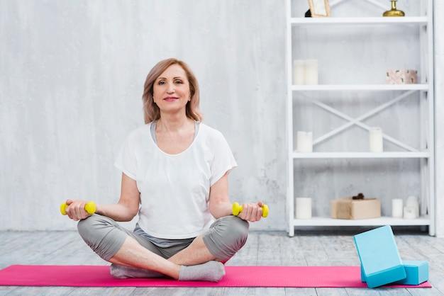 Retrato de una bella mujer sentada en una estera de yoga cerca de bloques sosteniendo pesas amarillas en casa