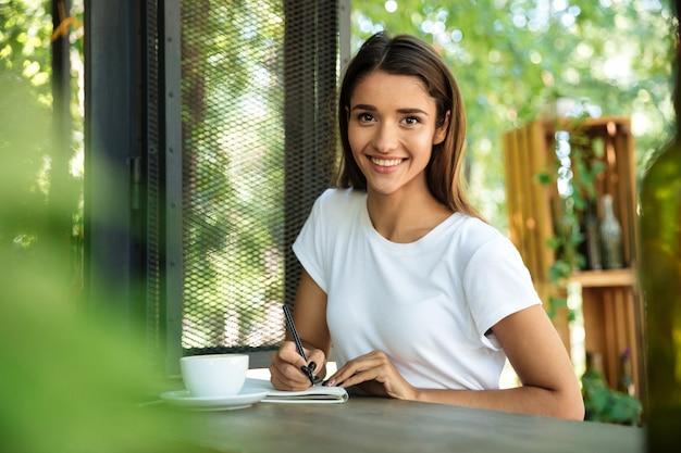 Retrato de una bella mujer sonriente haciendo notas