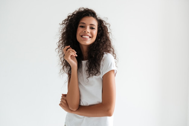 Retrato de una bella mujer sonriente con el pelo largo y rizado