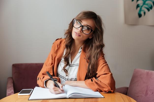 Retrato de una bella mujer tomando notas