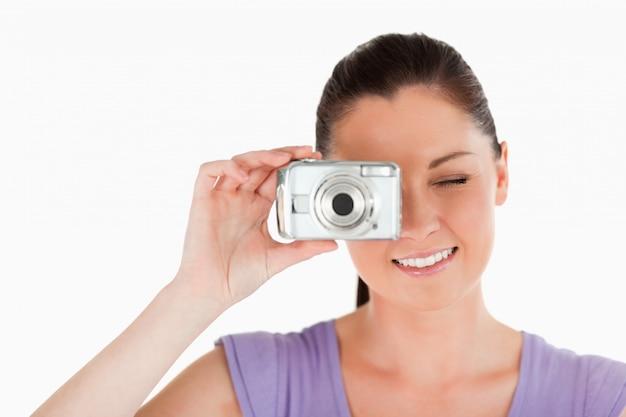 Retrato de una bella mujer usando una cámara mientras está de pie